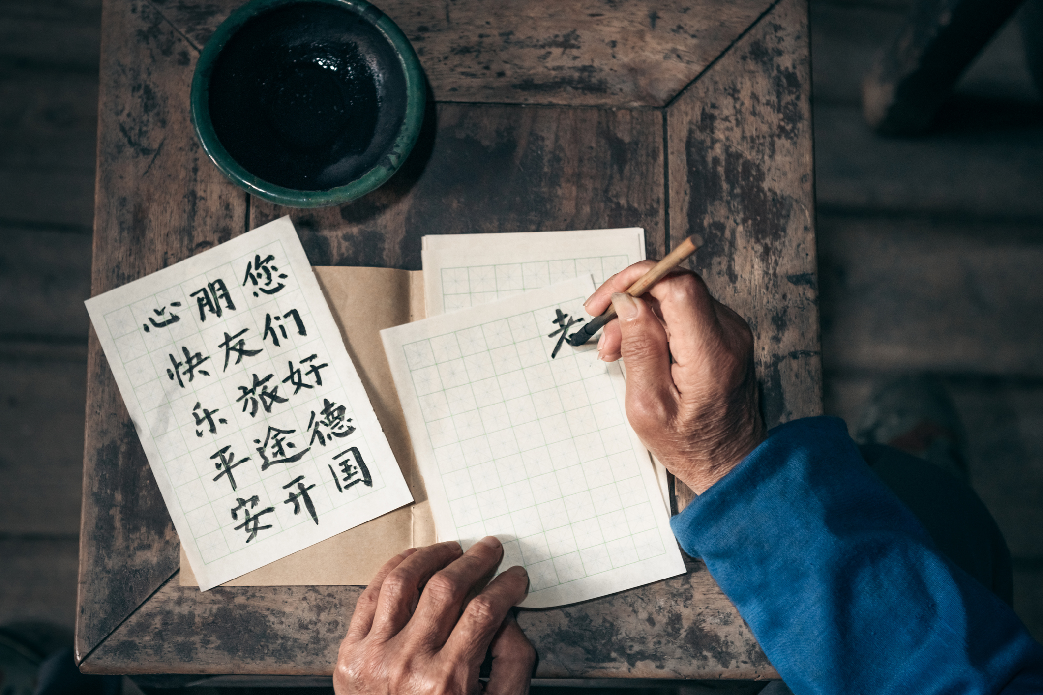 Chinese senior man writing Chinese calligraphy characters on paper.