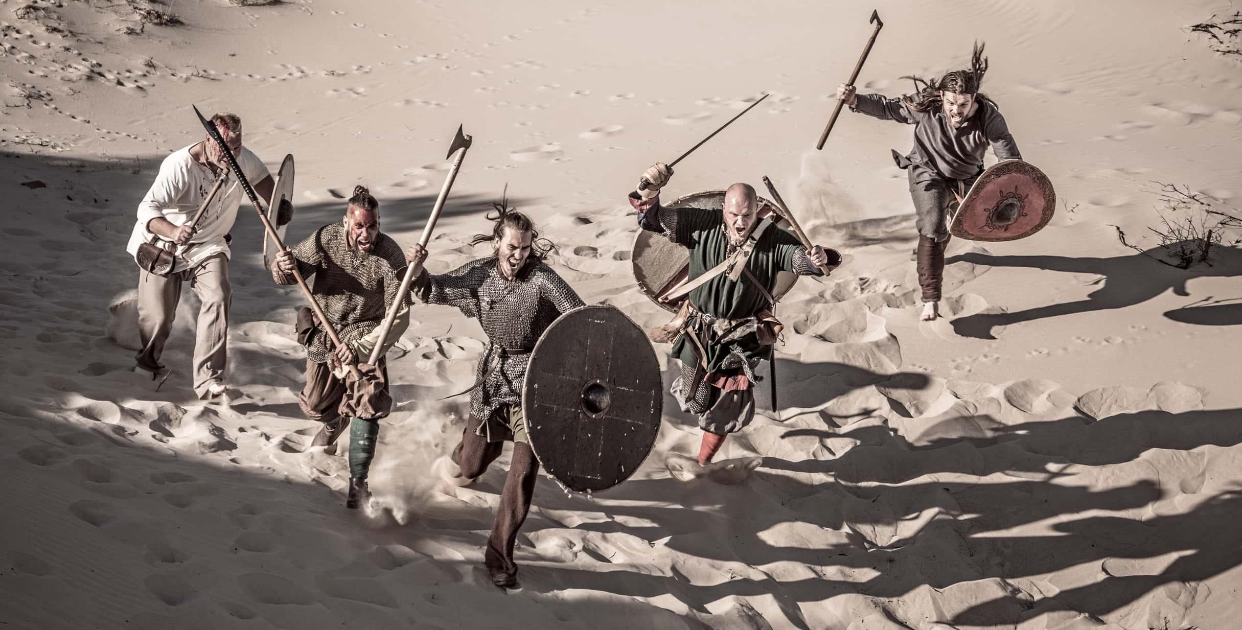 A hoard of Weapon wielding viking warriors on a sandy battlefield dune