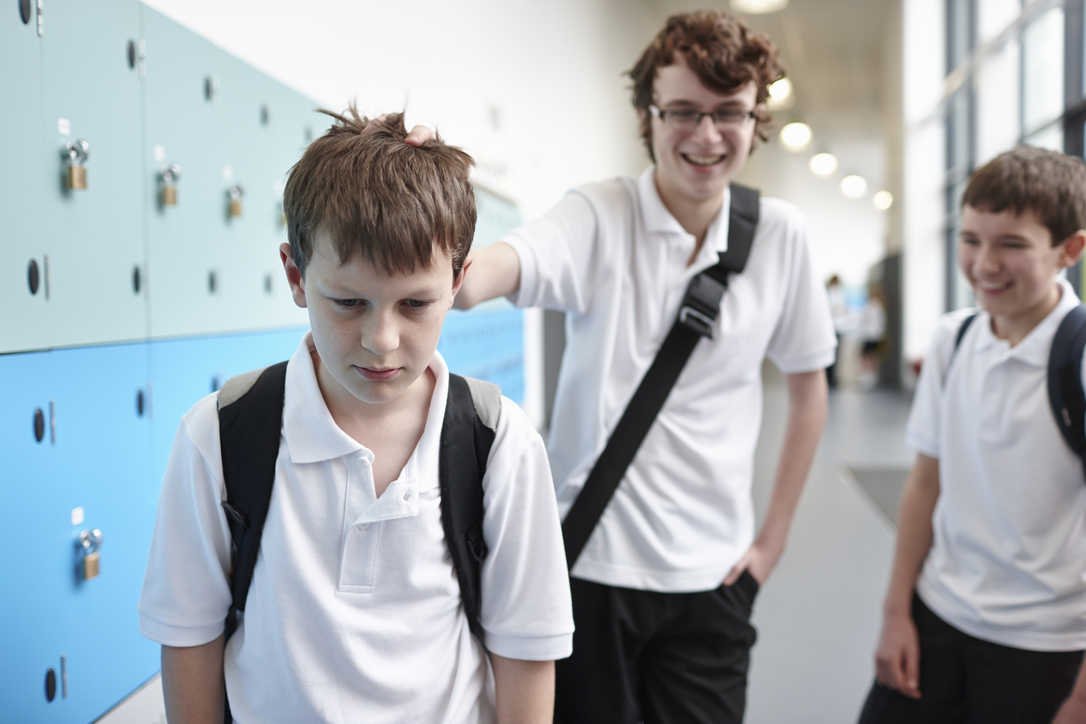 Schoolboy being bullied in school corridor.