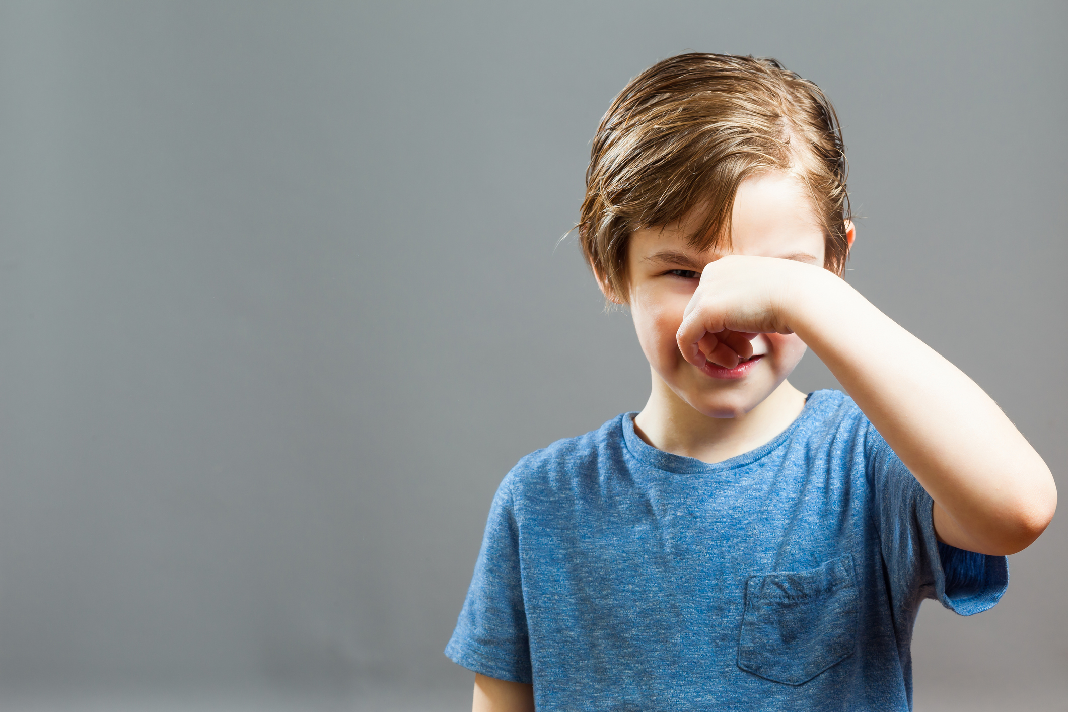 Boy Holding Nose While Standing Against Wall At Home