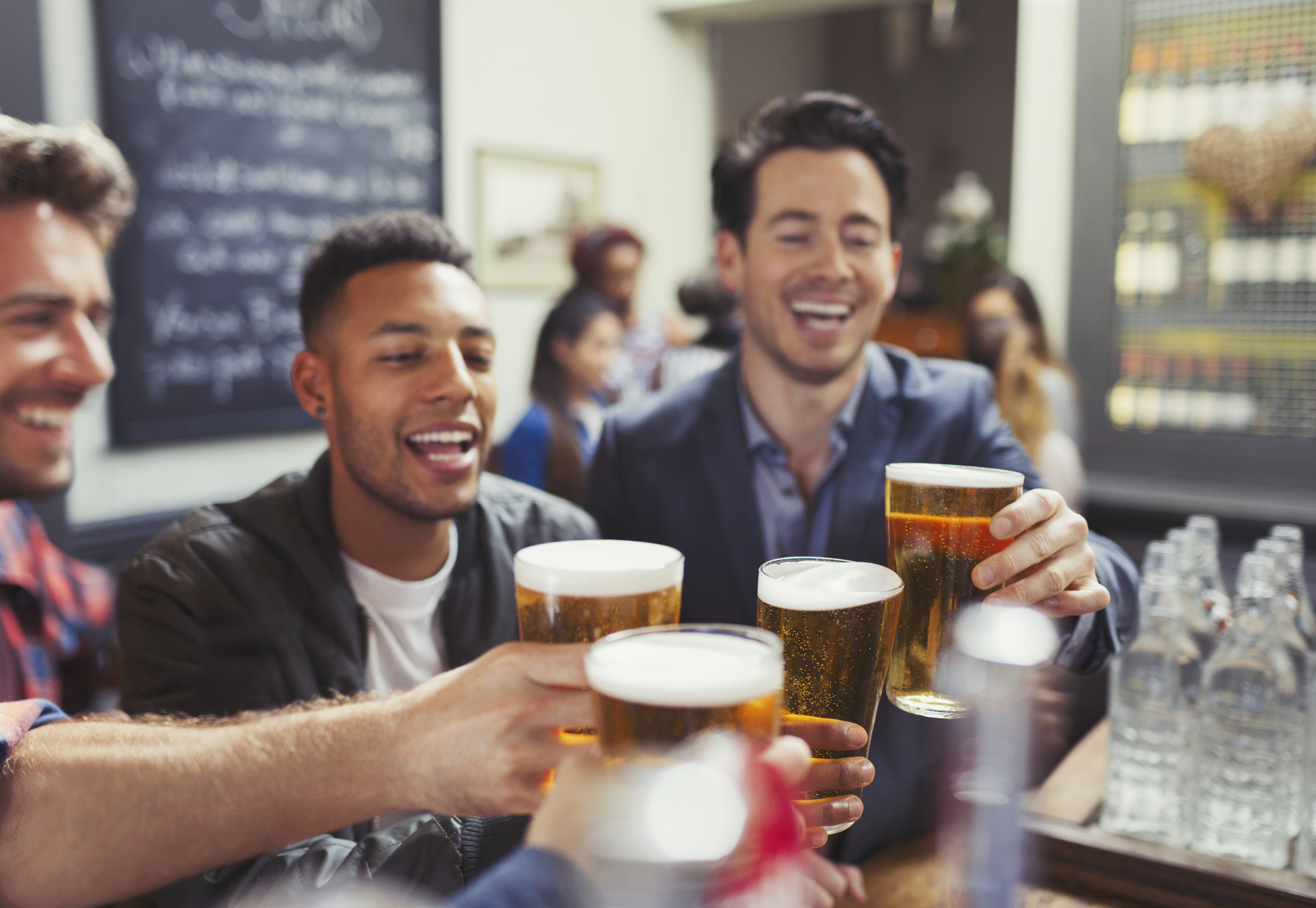 Male friends toasting beer glasses at bar.