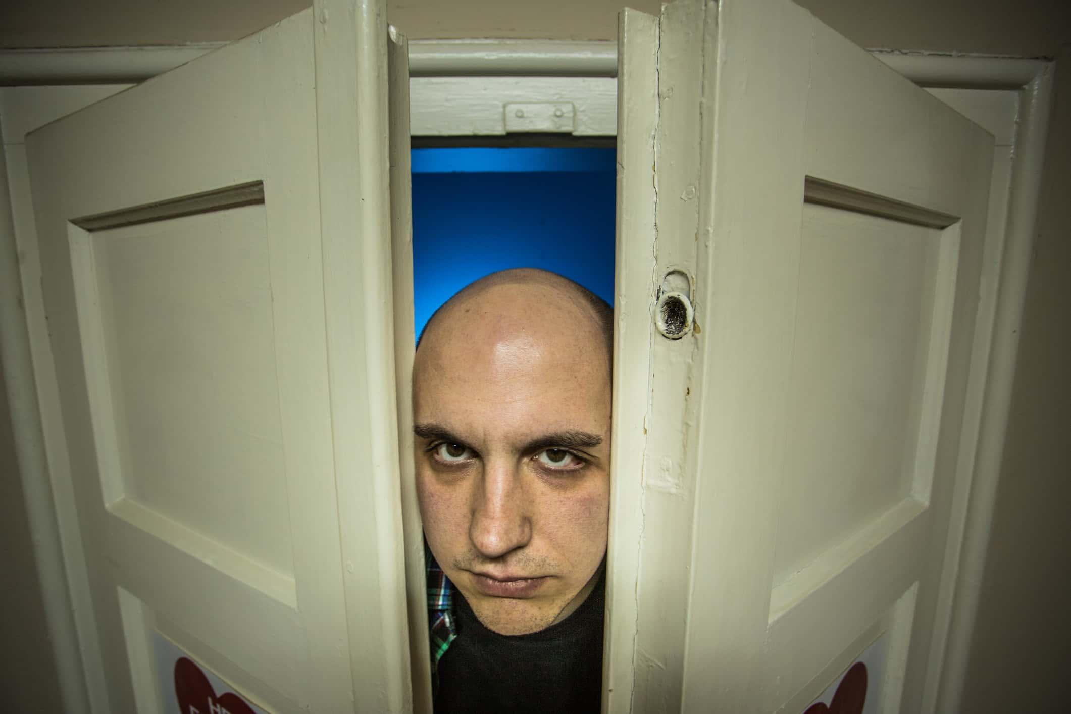 Creepy bald Man Staring At Camera through the door