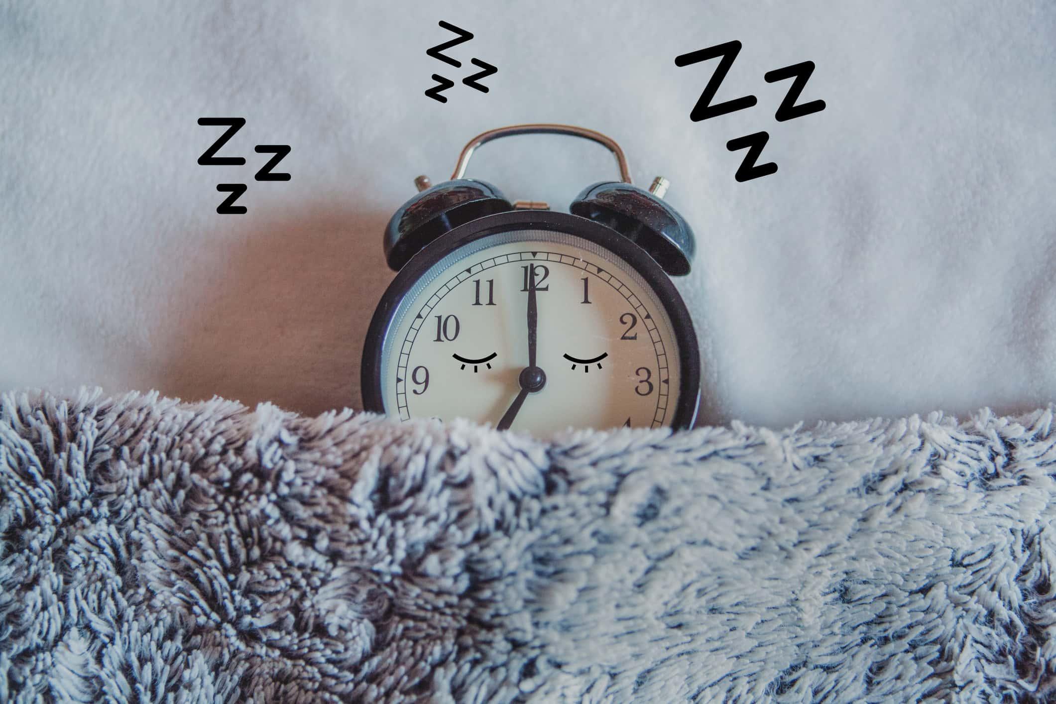 Alarm clock sleeping in bed.