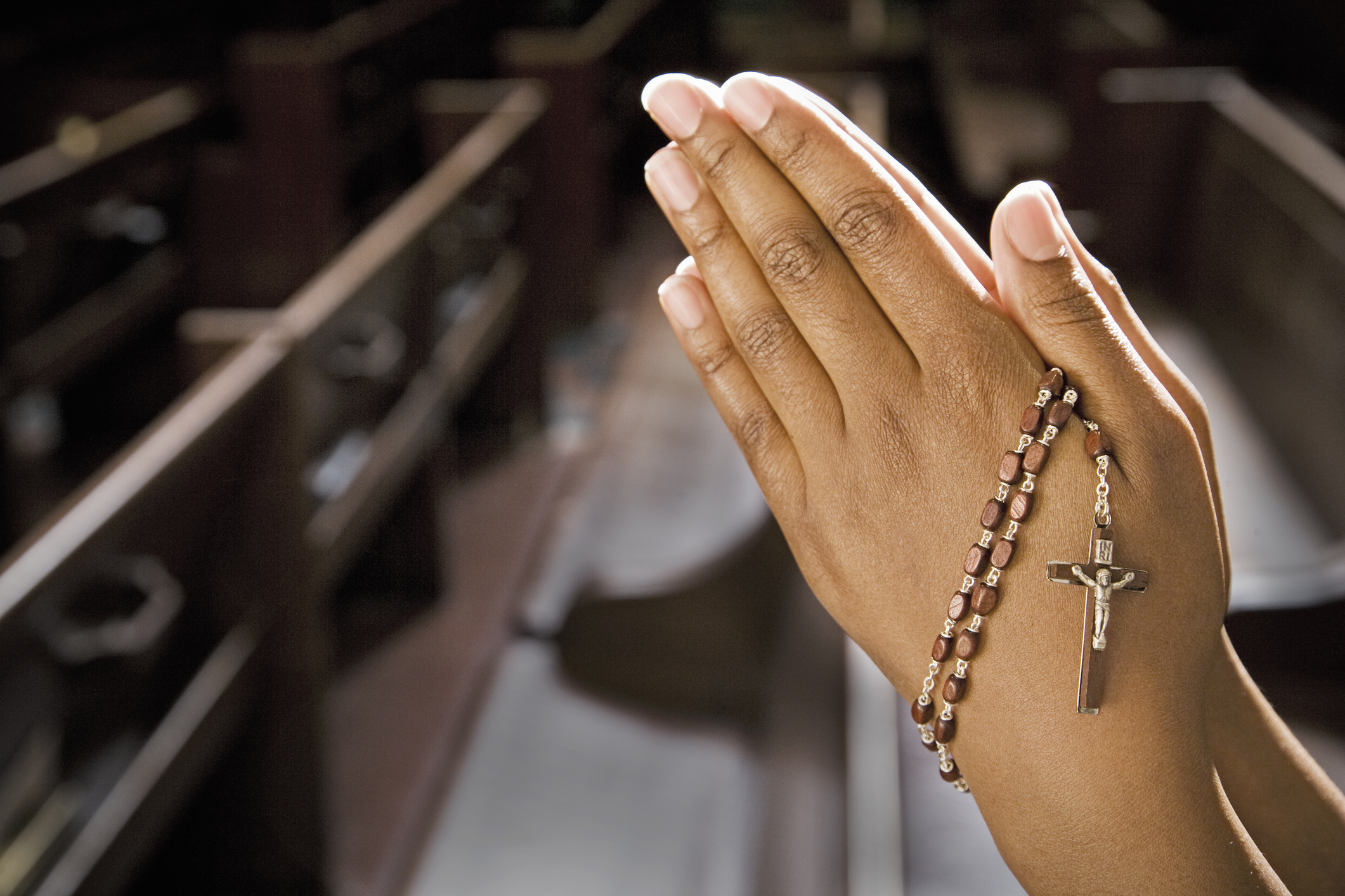 Hands Praying in Church With Rosary.
