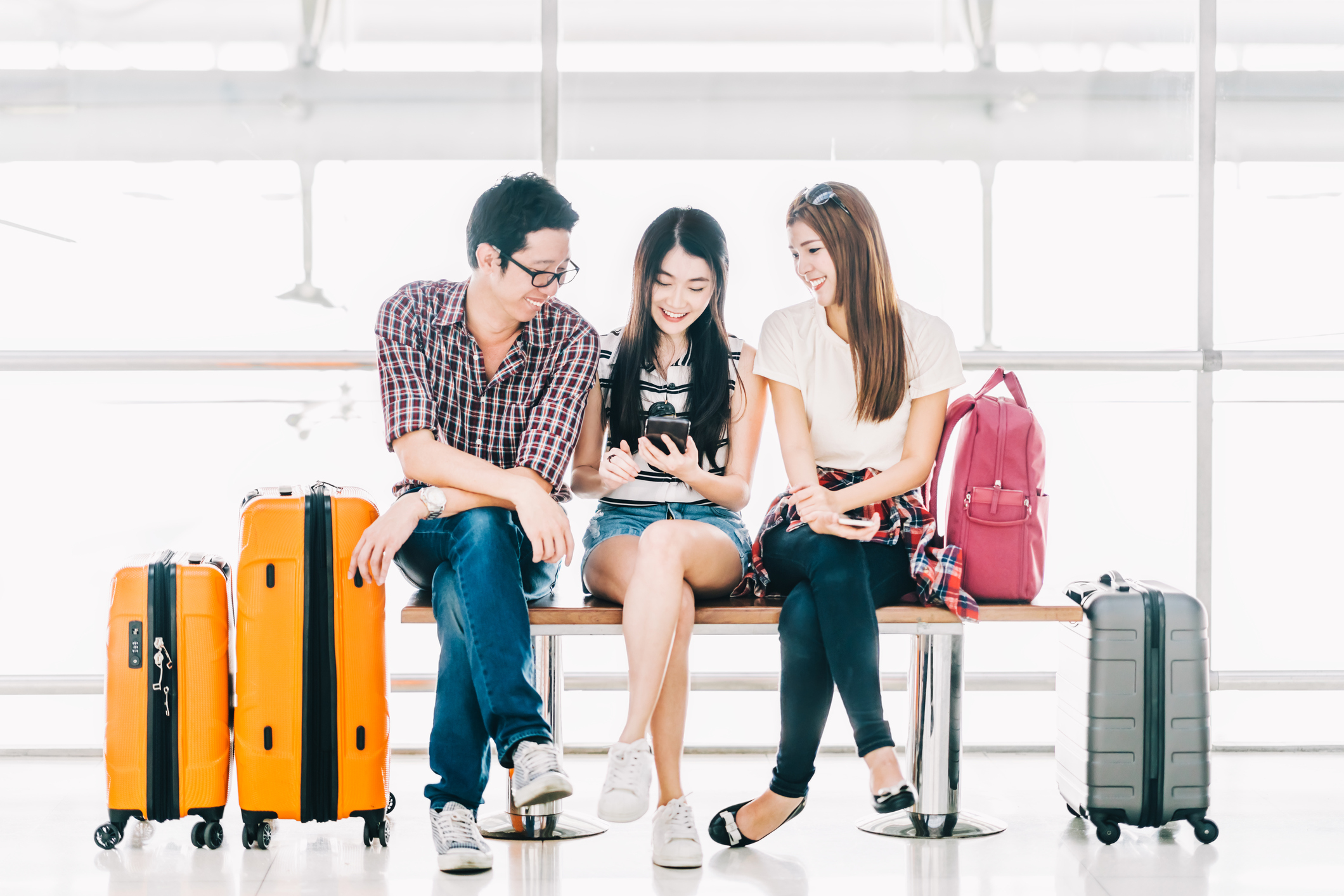 A group of young Asian people checking their mobile phones at the airport.