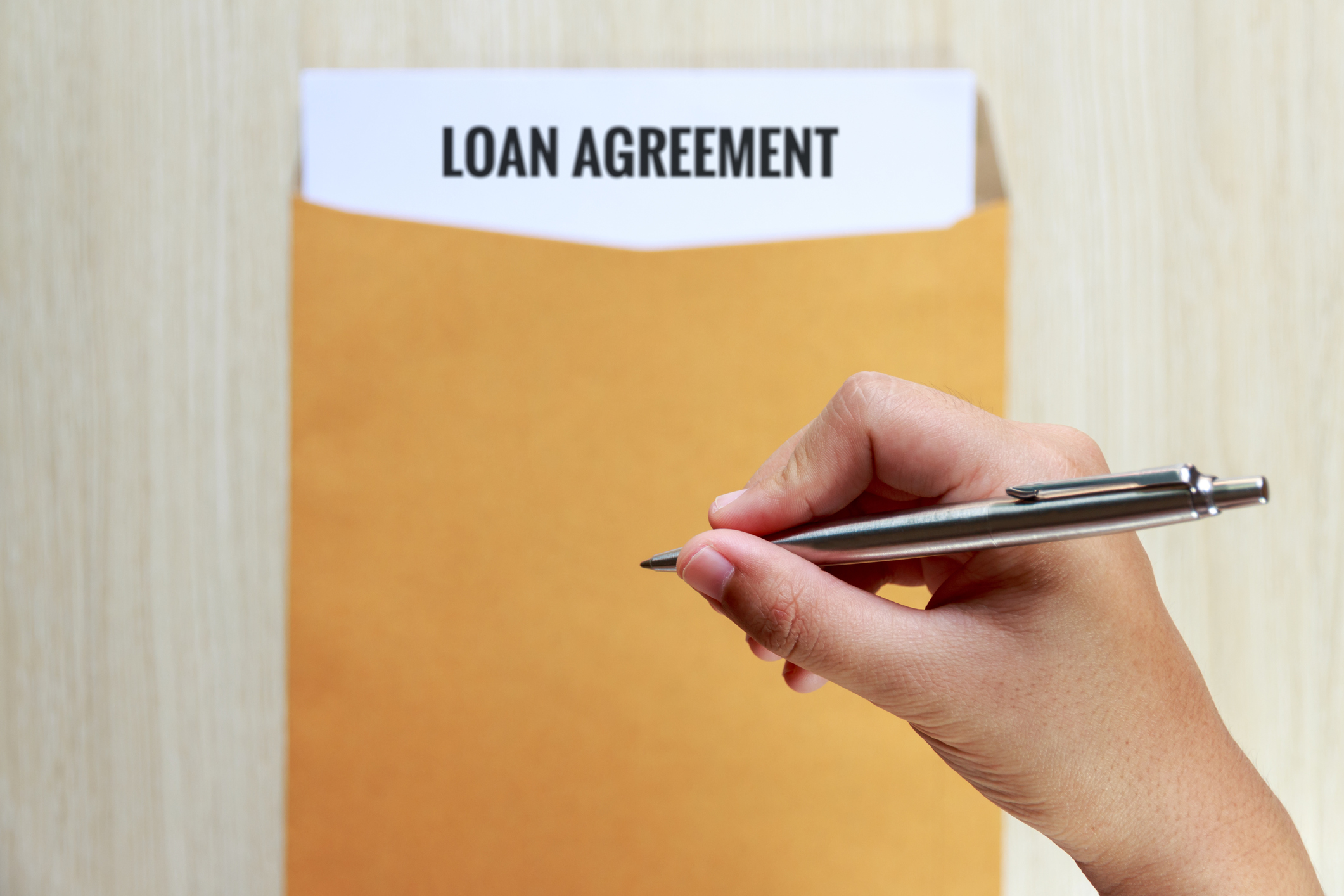 Hand Holding Pen Over Loan Agreement