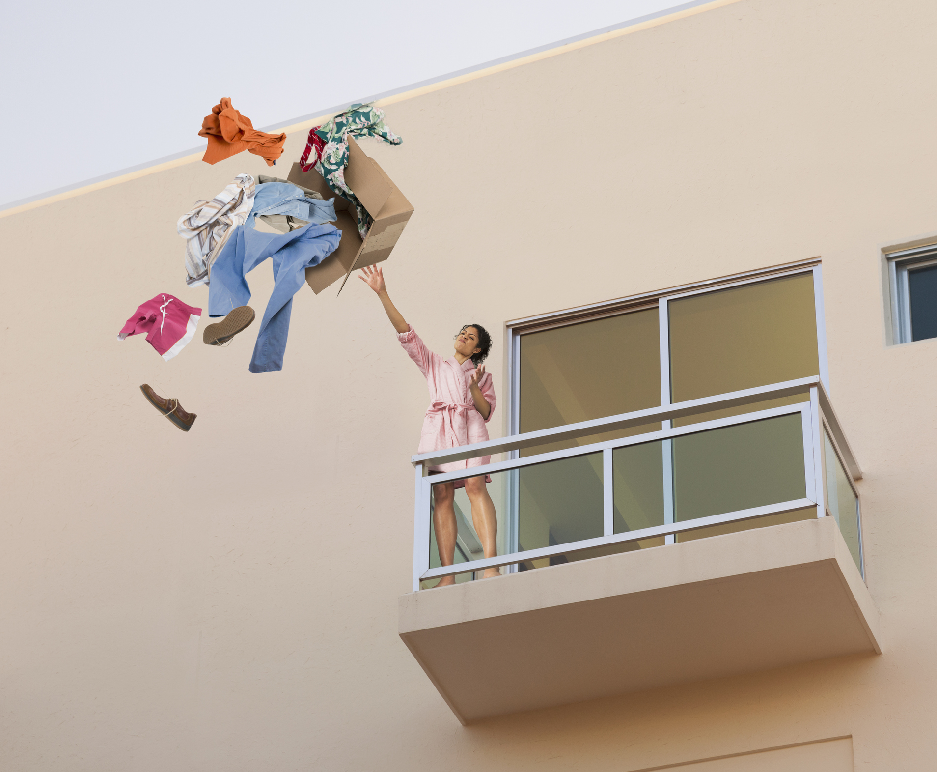 Mixed race woman throwing clothes off balcony.
