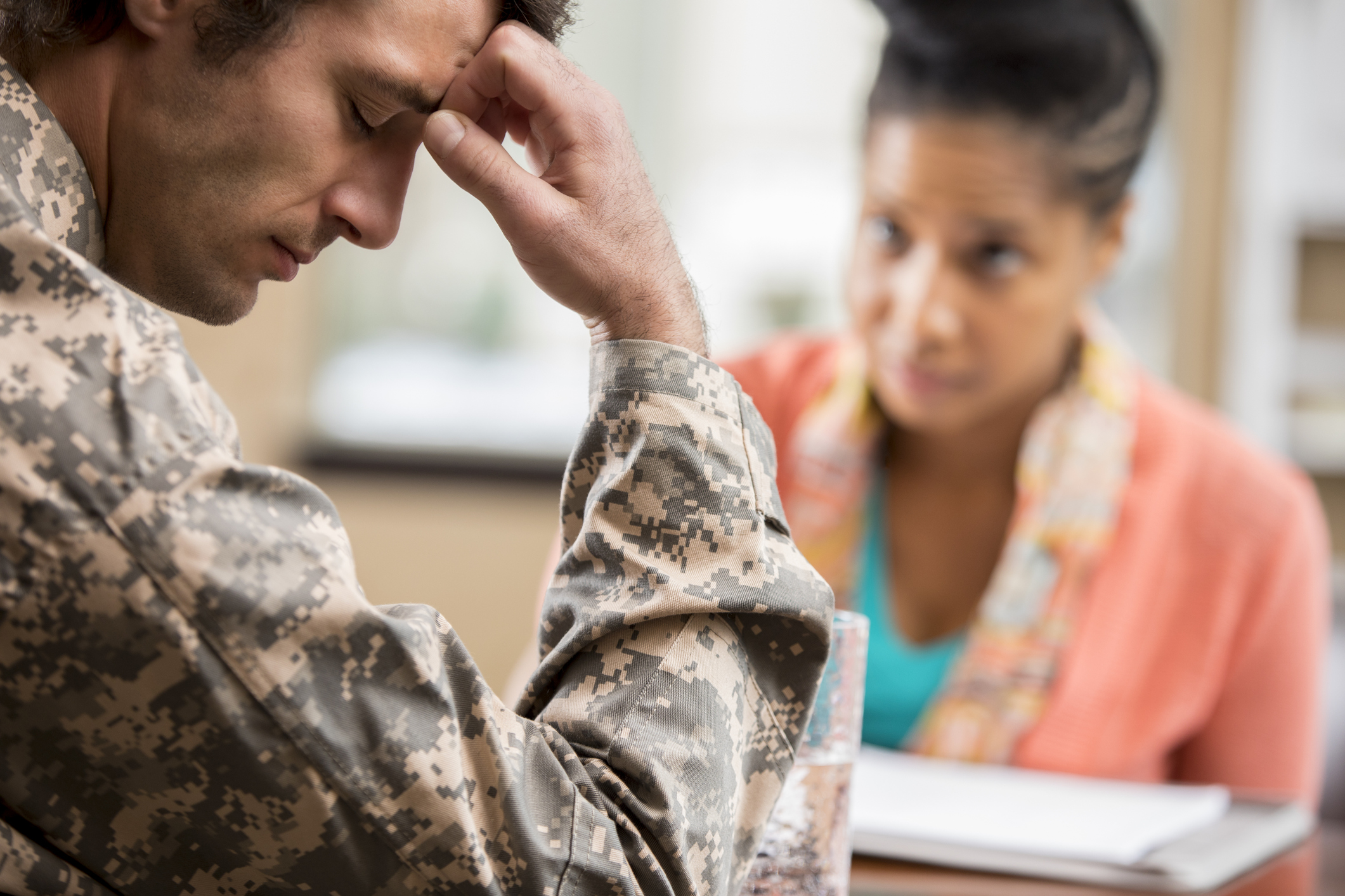 Depressed veteran meets with psychologist.