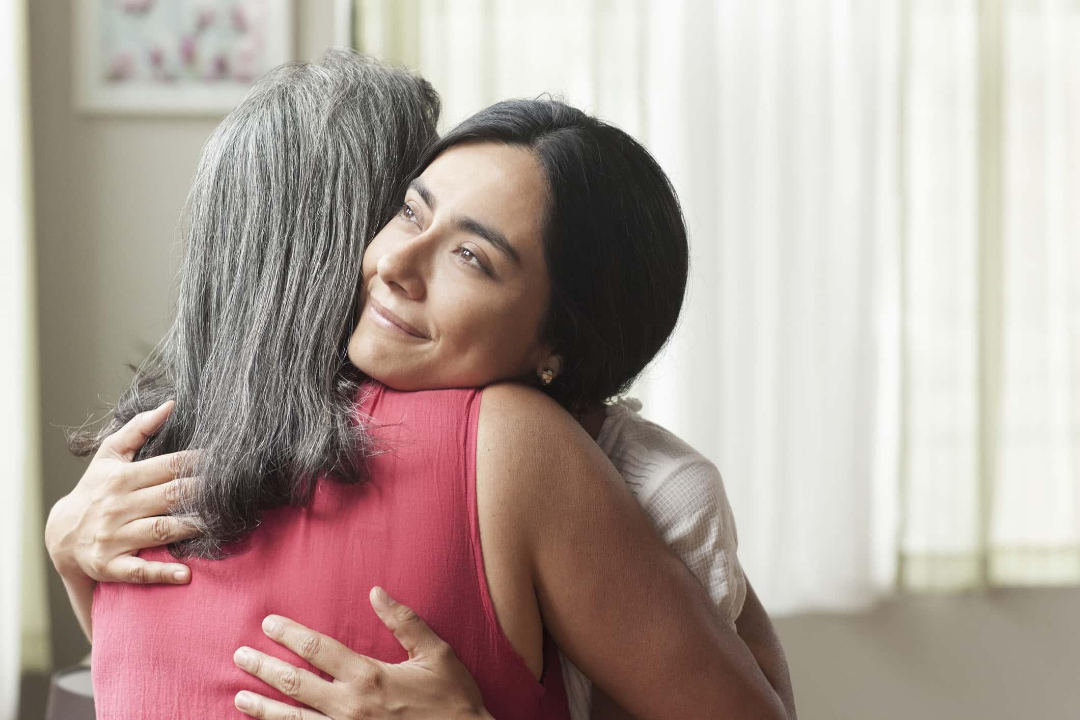 Smiling daughter hugging her mother
