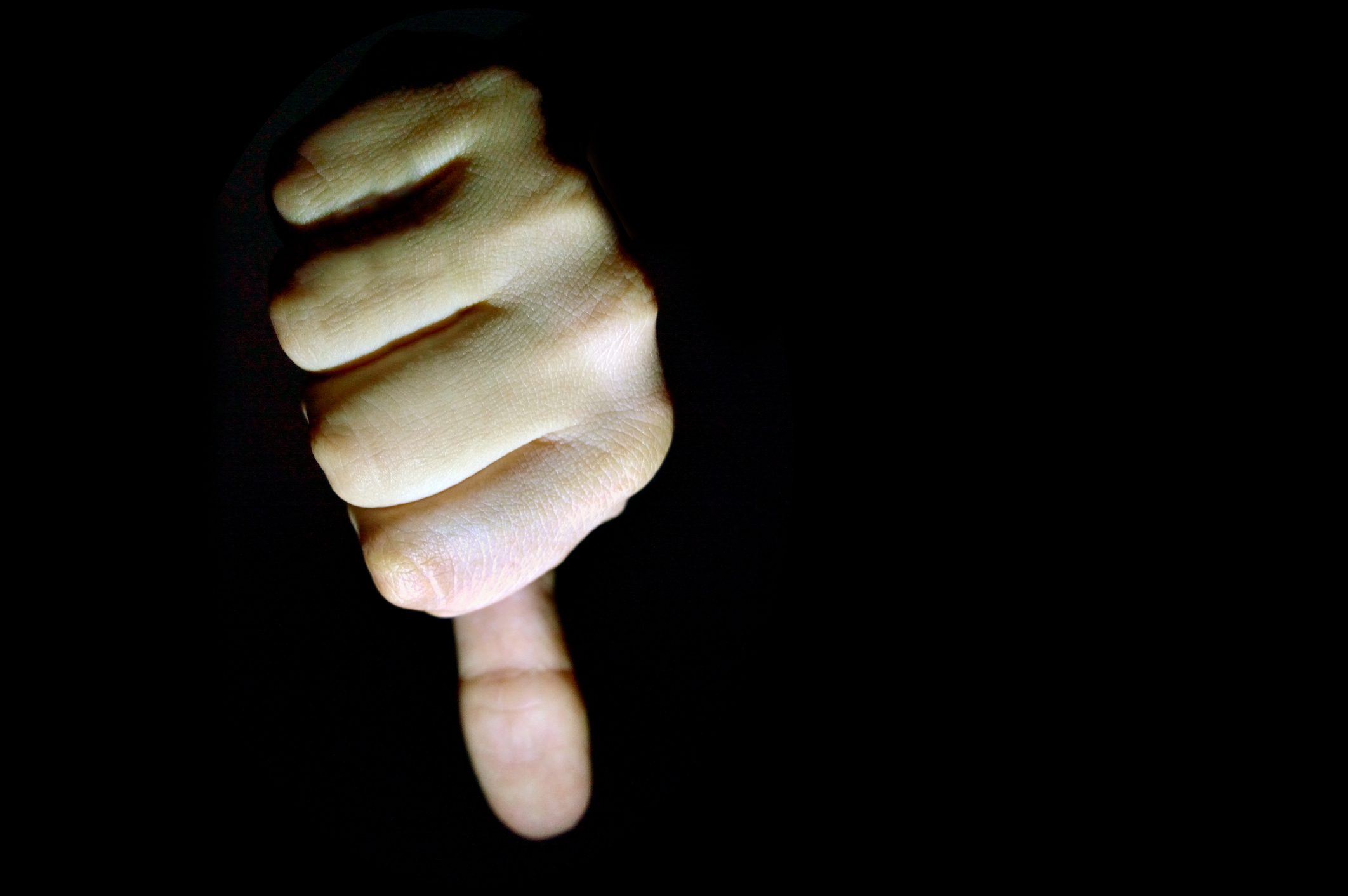 Close-Up Of Human Hand Gesturing Thumbs Down.