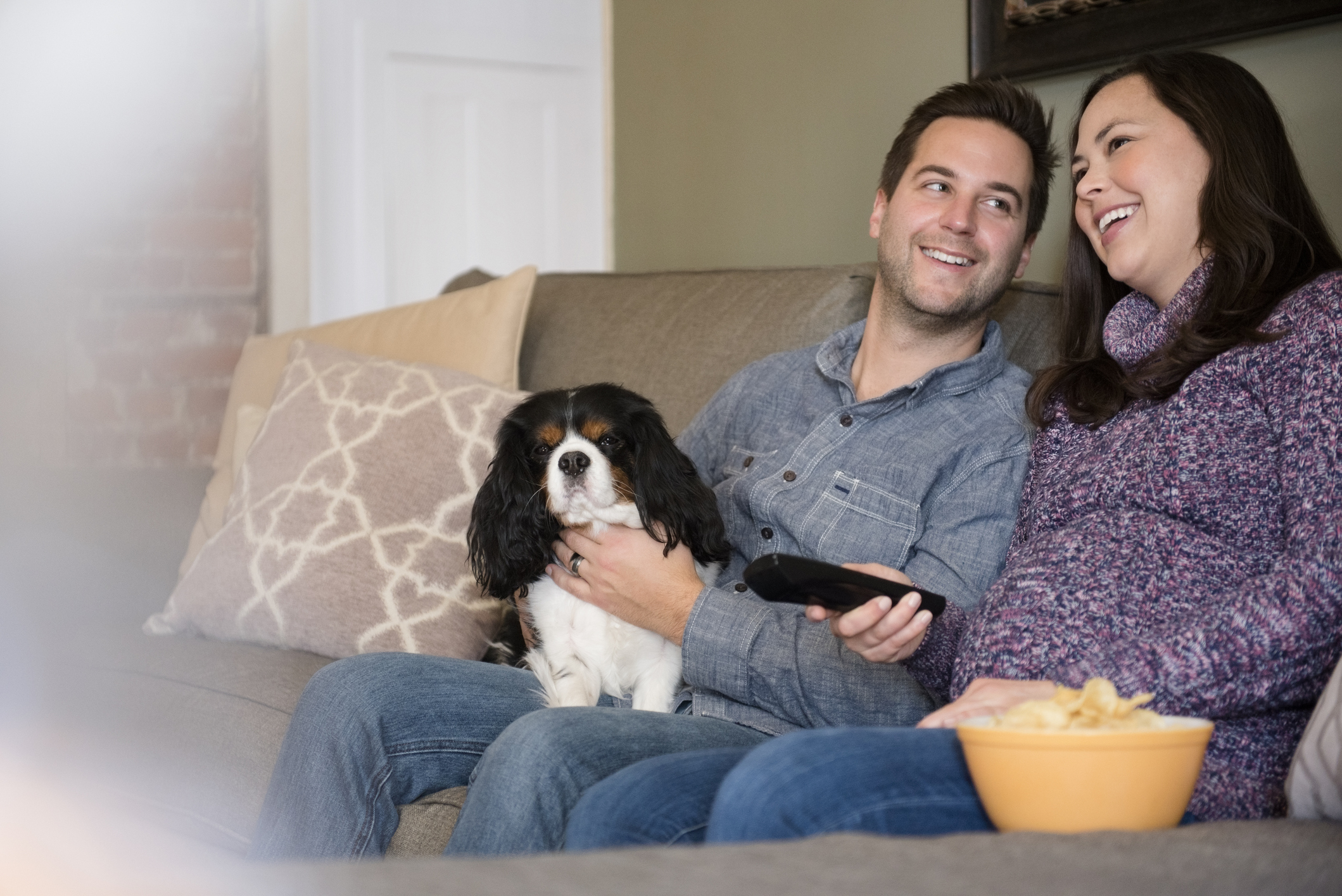 Happy mid adult couple relaxing on sofa with dog.