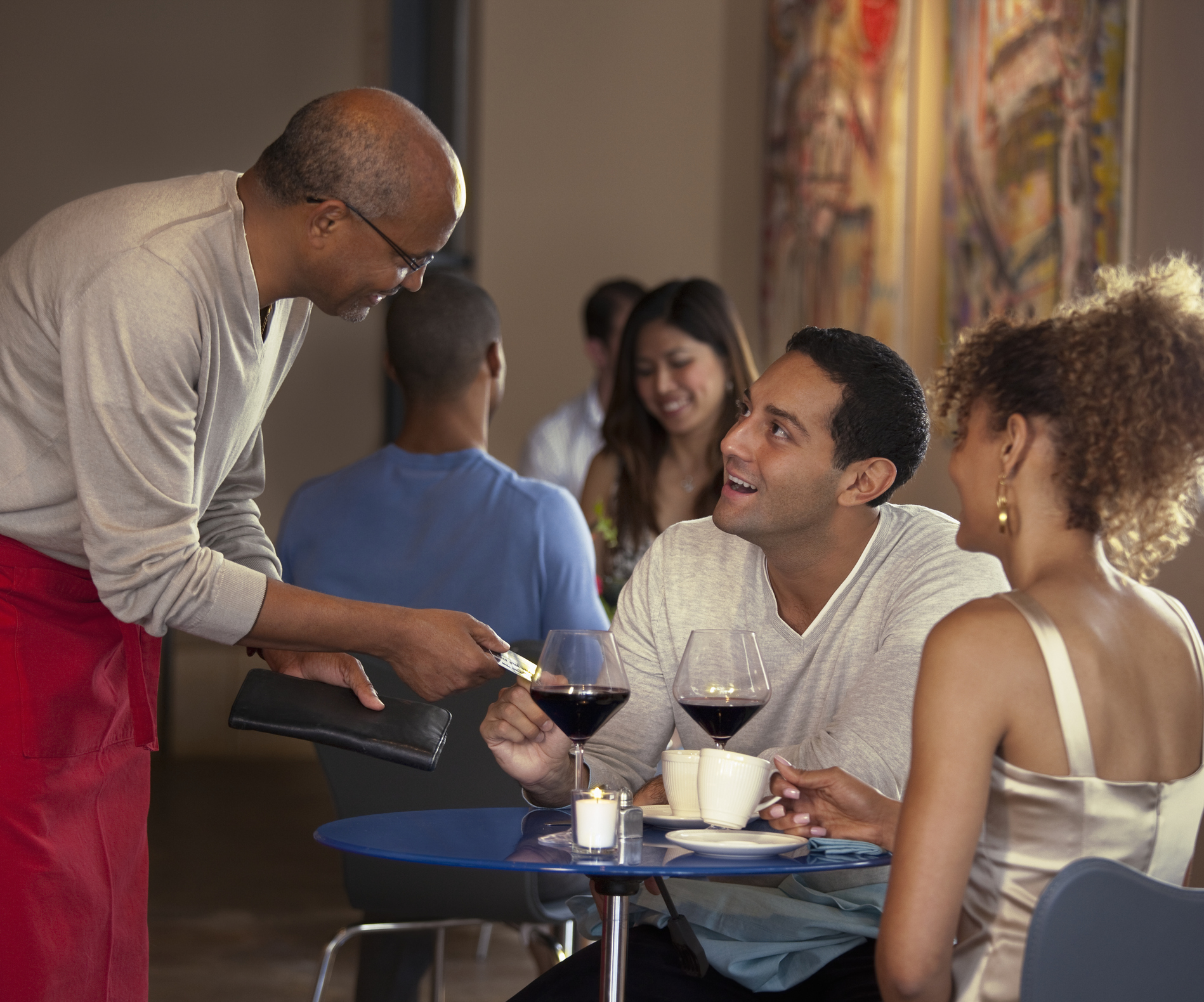 Customers paying waiter at restaurant.