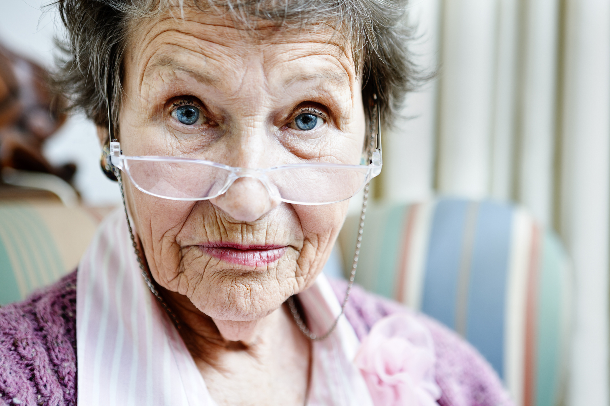 Old lady looks over spectacles with eyebrows raised.
