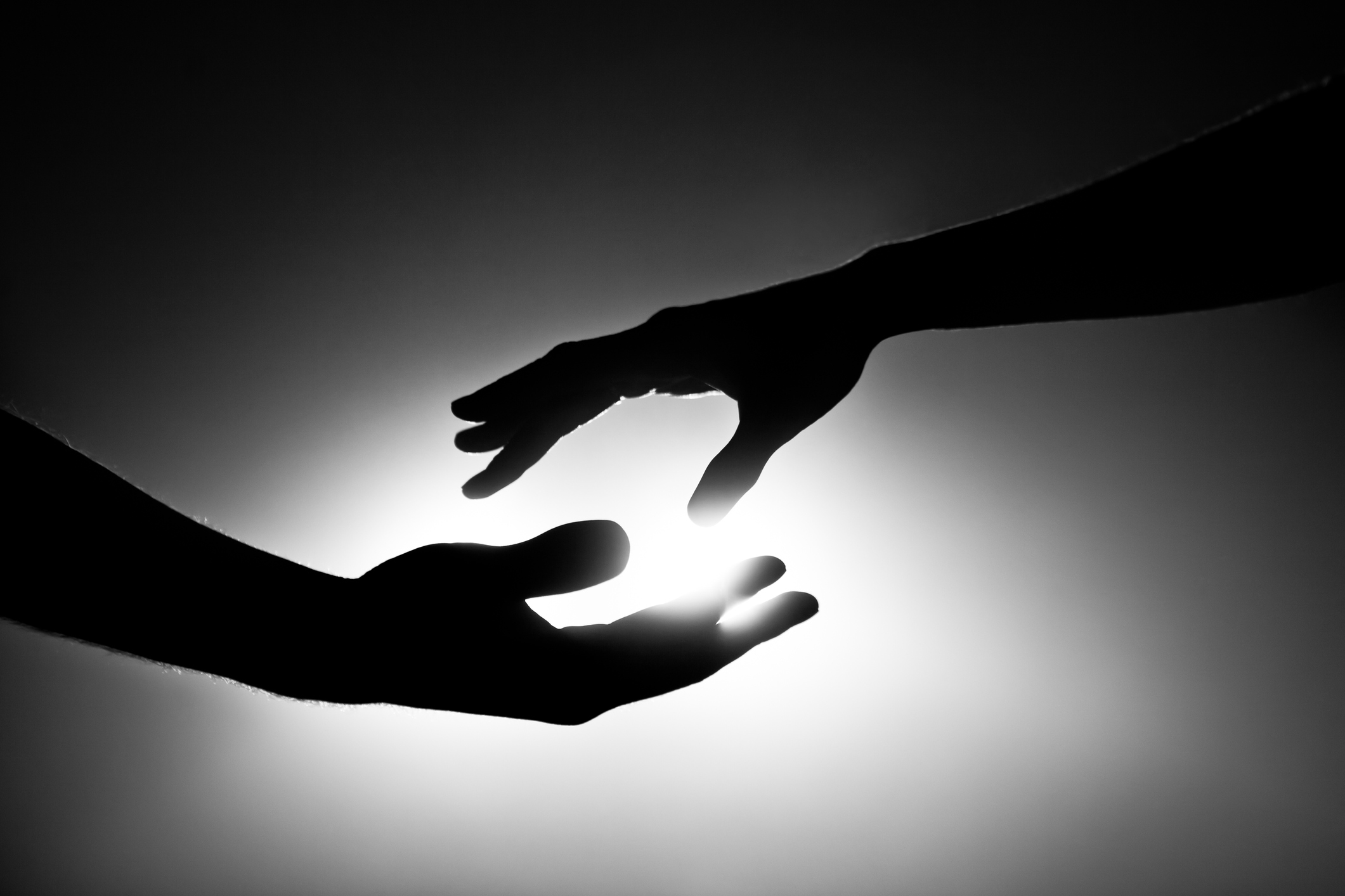 Black and white image of two hands reaching out.