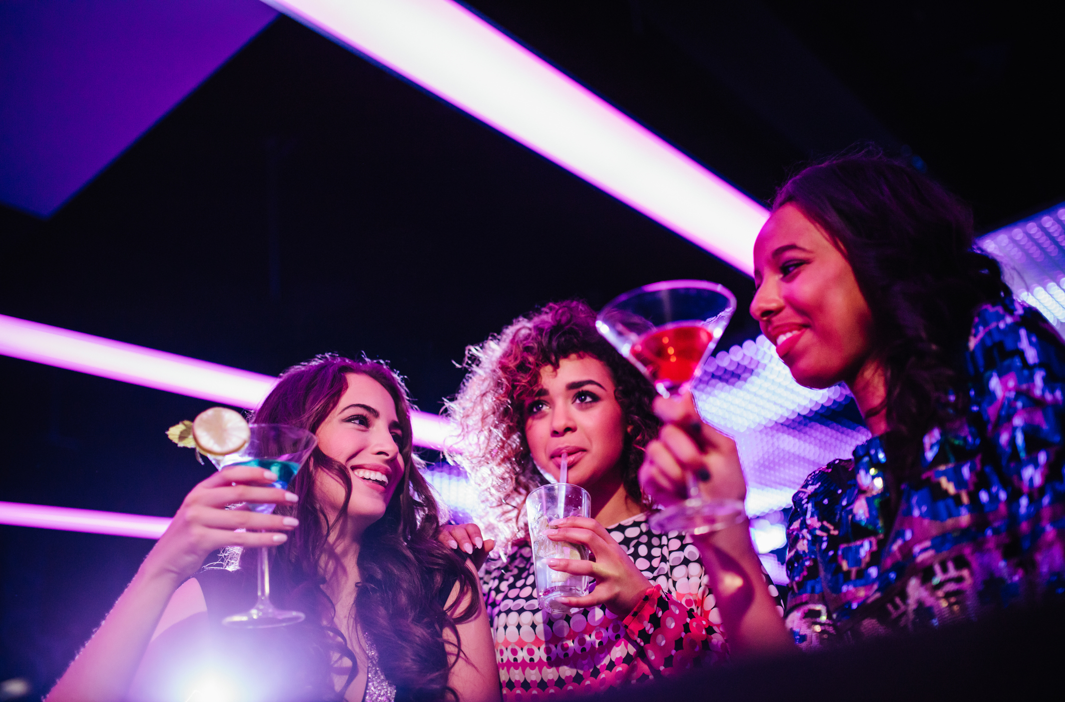 Young friends enjoying party with drinks at the club.