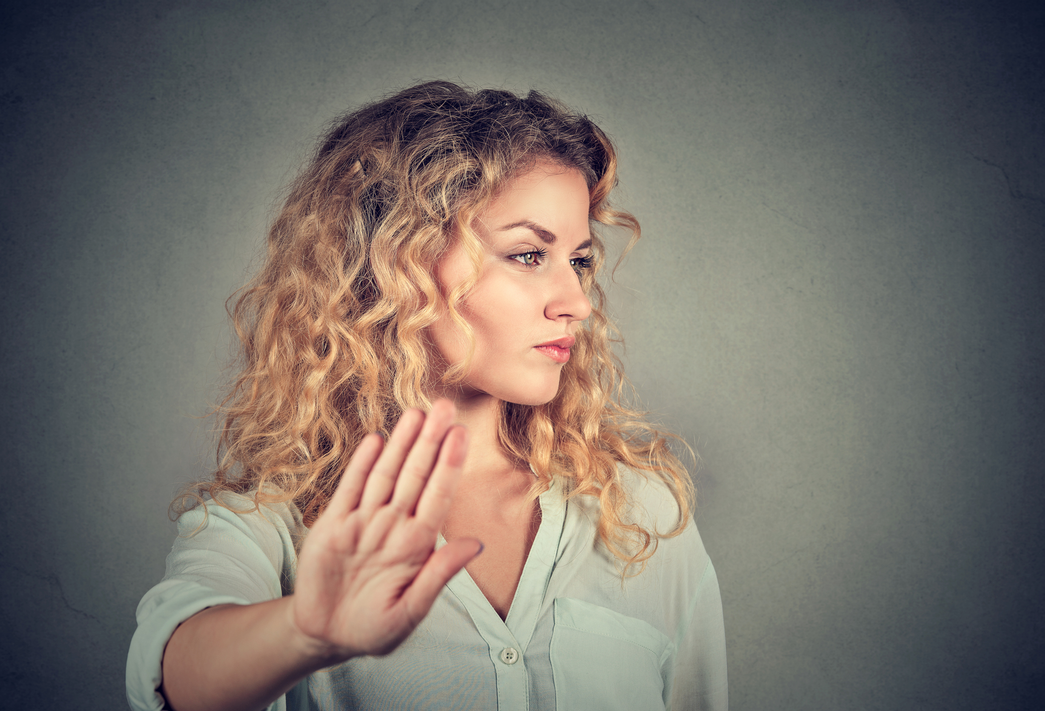 Annoyed woman with bad attitude giving talk to hand gesture.