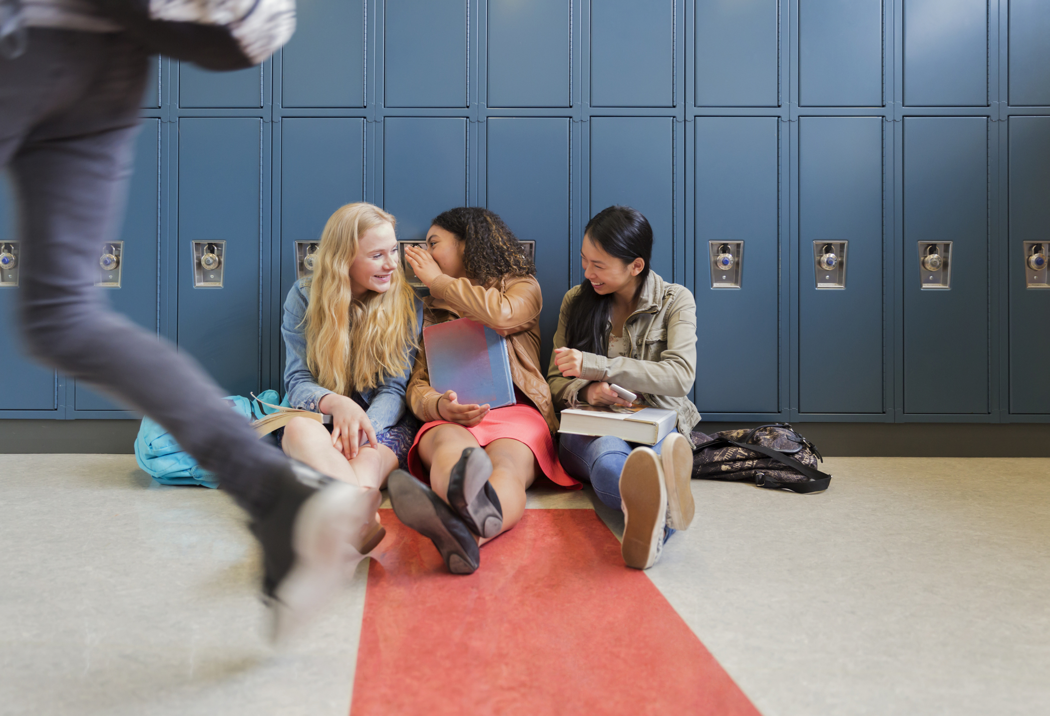 Students gossiping in school hallway.