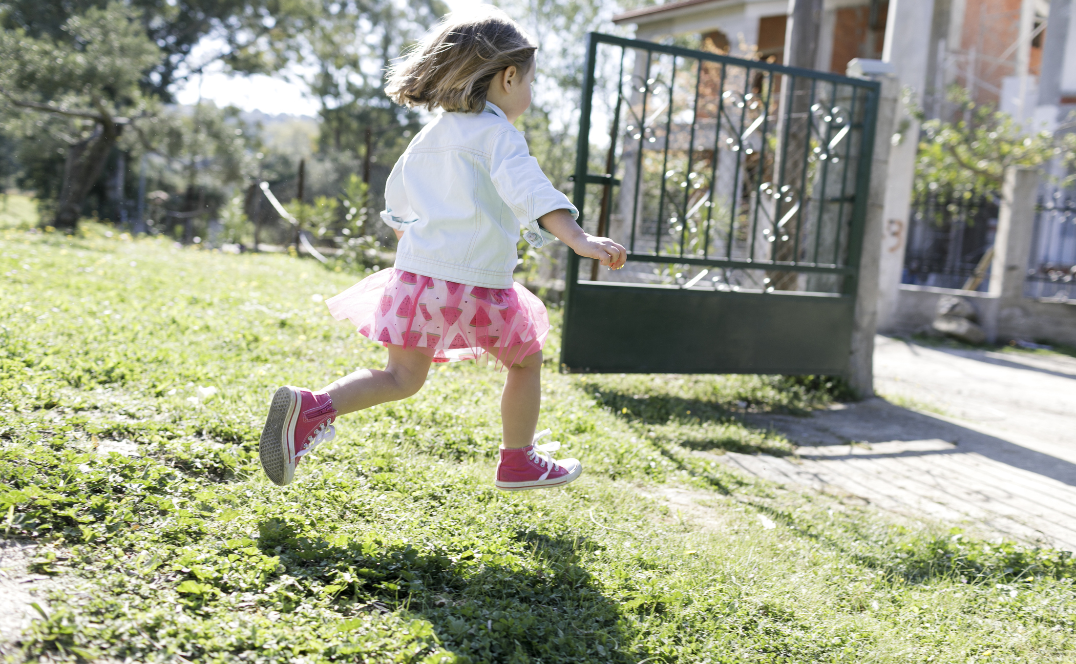 Little girl running on meadow in the garden.
